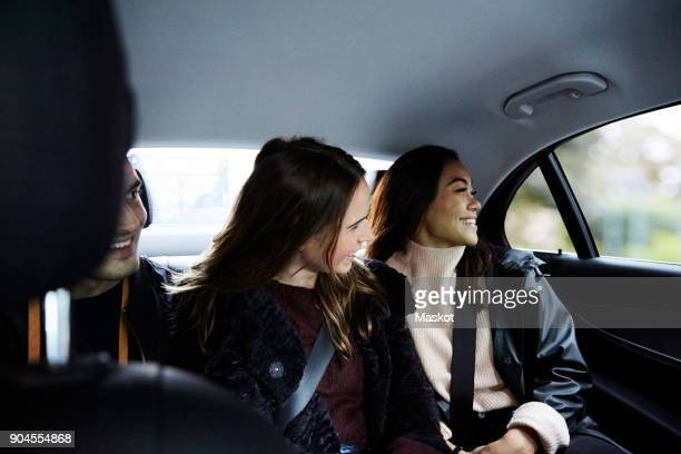 Smiling friends traveling in car at city