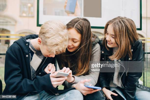 smiling friends using mobile phone while sitting at bus stop - adolescence stock pictures, royalty-free photos & images