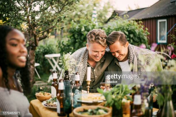 smiling homosexual couple using phone at garden party - lgbtq  and female domestic life fotografías e imágenes de stock