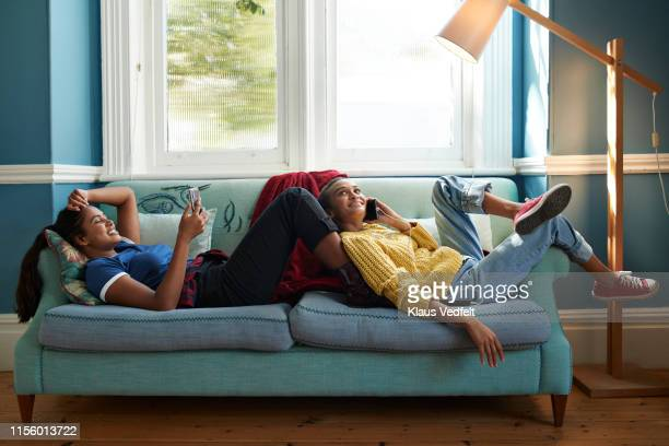 smiling friends using phone while lying on sofa - 可動性 ストックフォトと画像