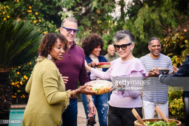 smiling friends walking into backyard dinner party with food - guest stock pictures, royalty-free photos & images