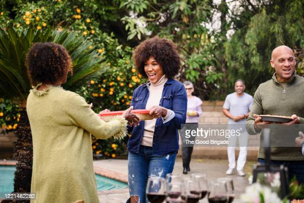 smiling friends walking into backyard party with trays of food - ポットラック ストックフォトと画像
