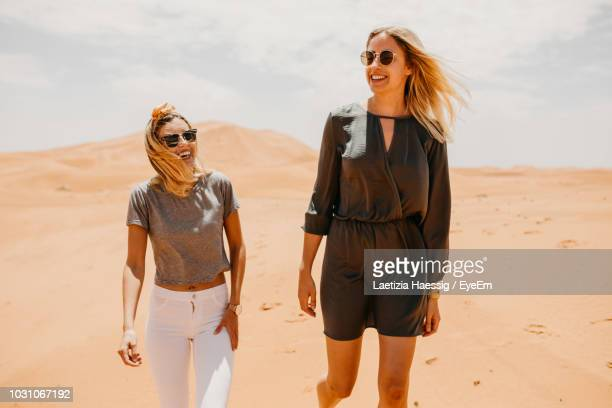 smiling friends walking on desert in sunny day - femme marocaine photos et images de collection