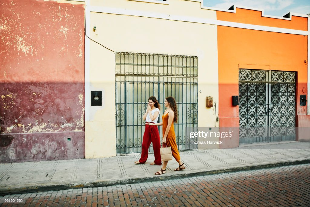 Smiling friends walking through colorful town while shopping during vacation : Stock Photo