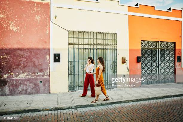 smiling friends walking through colorful town while shopping during vacation - red pants stock pictures, royalty-free photos & images