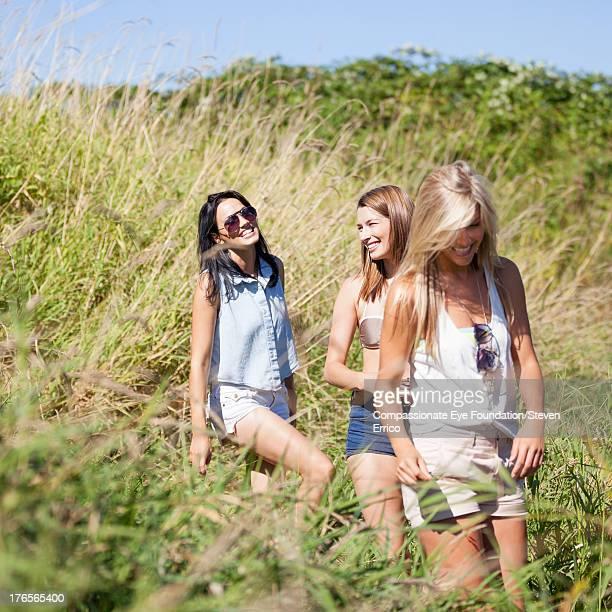 Smiling friends walking through meadow