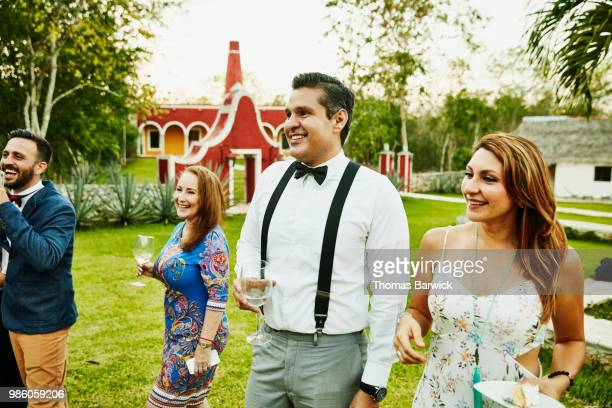 smiling friends watching bride and groom cut cake during outdoor wedding reception - wedding guest stock pictures, royalty-free photos & images