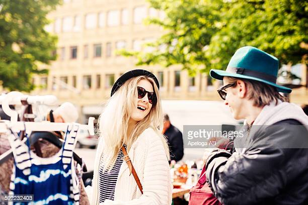 Smiling friends wearing hat and sunglasses standing at flea market