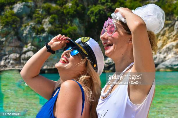 smiling friends wearing sunglasses at beach - sailor hat stock pictures, royalty-free photos & images