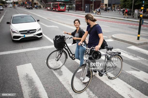 Smiling friends with bicycles crossing city street