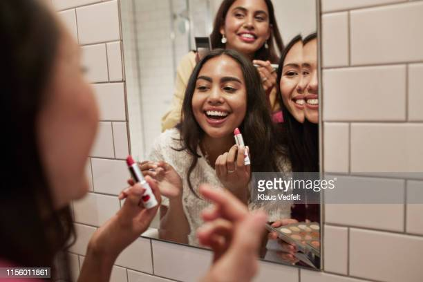 smiling friends with lipstick looking at mirror - make up stockfoto's en -beelden