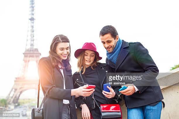 Lächelnd Freunde, die mit smartphones nahe dem Eiffelturm
