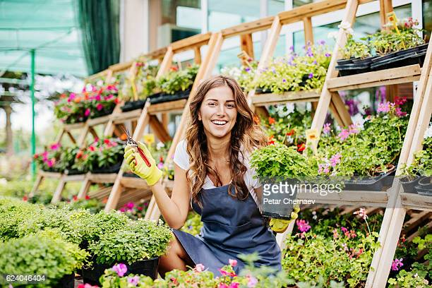 Smiling gardener holding pruners and a potted plant