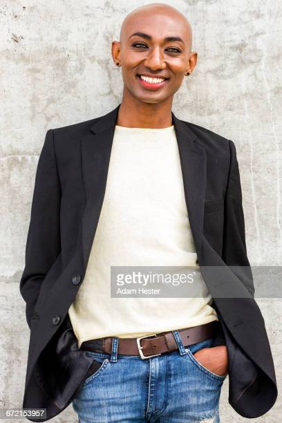 Smiling gay Black man leaning on concrete wall