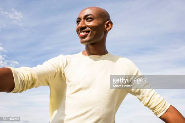 smiling gay black man under cloudy sky - androgynous stock pictures, royalty-free photos & images