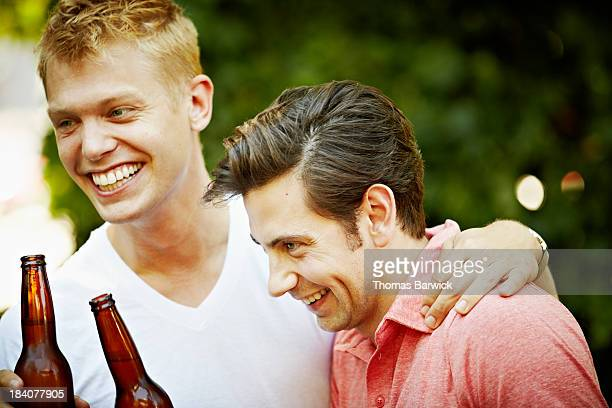 Smiling gay couple embracing and laughing