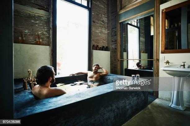 Smiling gay couple enjoying bath in hotel spa