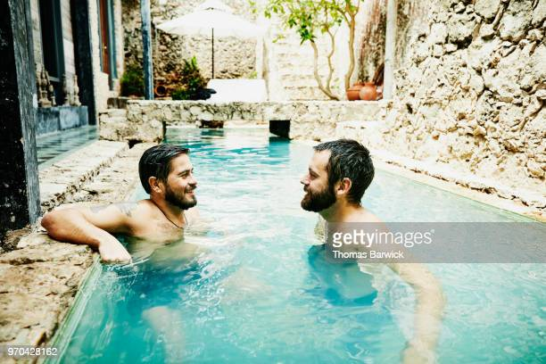 Smiling gay couple hanging out together in courtyard pool at boutique hotel