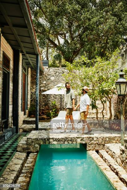 Smiling gay couple holding hands and walking across bridge over pool in courtyard of boutique hotel