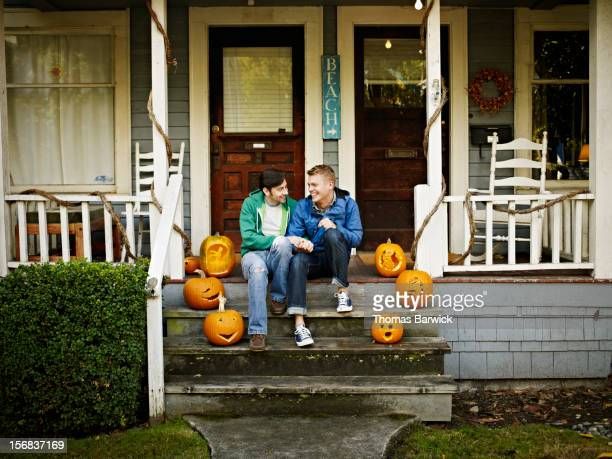 Smiling gay couple holding hands on front porch