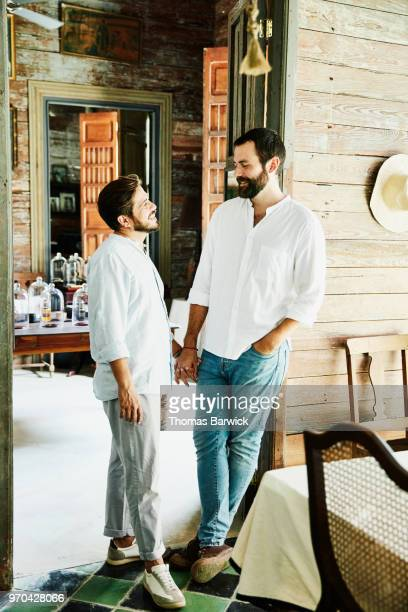 Smiling gay couple holding hands while standing in boutique hotel