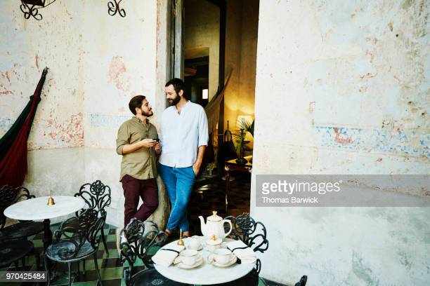 Smiling gay couple in discussion while standing in outdoor cafe