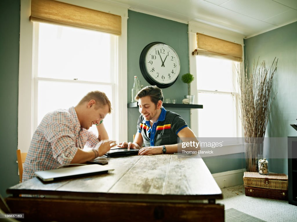 Smiling gay couple playing on digital tablet : Stock Photo
