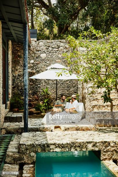Smiling gay couple sharing coffee while sitting in lounge chairs by pool in courtyard of boutique hotel