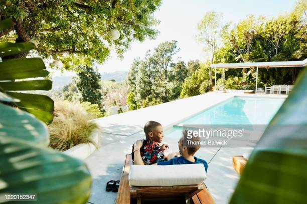 smiling gay couple sitting together on lounge chair on pool deck of vacation rental - beautiful gay men photos et images de collection