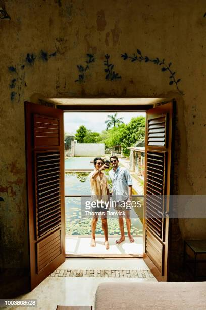 Smiling gay couple standing on balcony of luxury hotel room taking selfie with smartphone