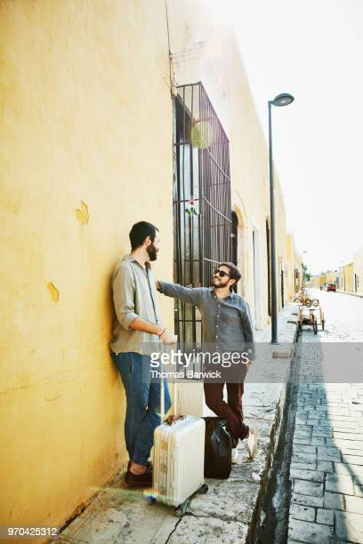 Smiling gay couple standing on street in discussion while exploring small town during vacation