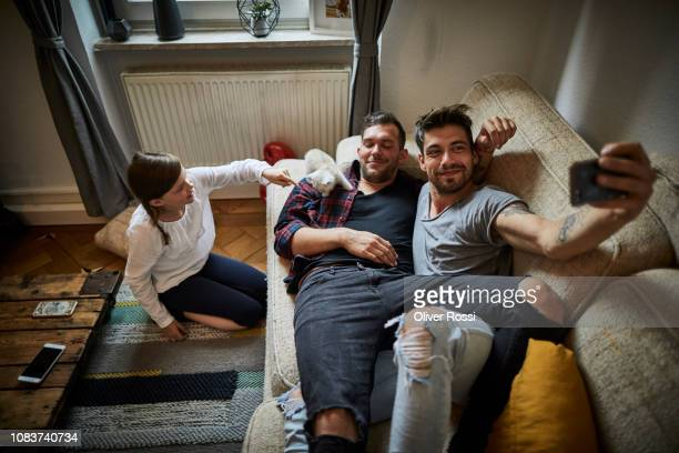 Smiling gay couple taking a selfie with girl and kitten at home