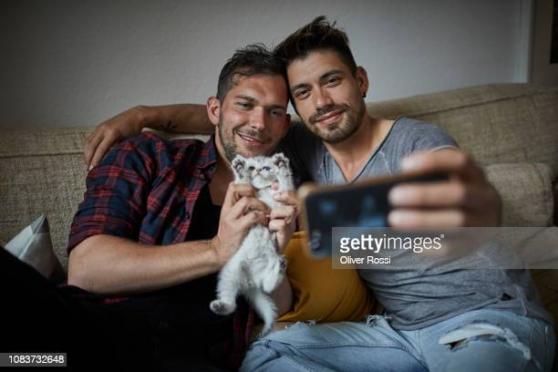 Smiling gay couple taking a selfie with kitten at home