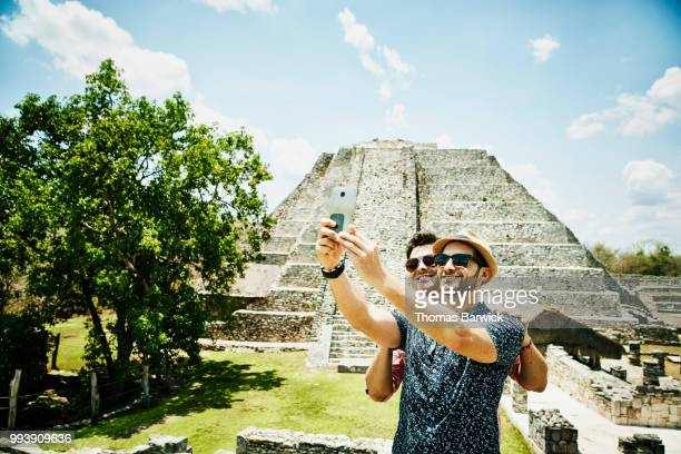 Smiling gay couple taking selfie with smartphone while exploring Mayapan ruins during vacation