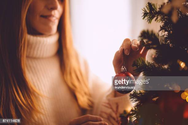 smiling ginger woman decorating christmas tree with red christmas ball - ornato foto e immagini stock
