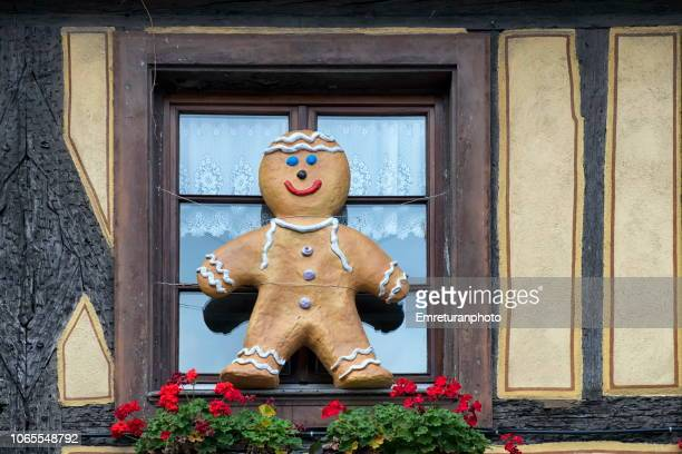 Smiling gingerbread cookie sign on a window.