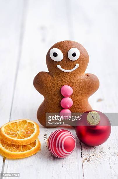 Smiling gingerbread man, orange slices and two christmas baubles on white wood