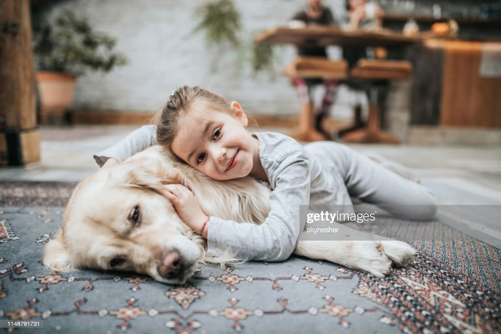 Smiling girl and her golden retriever on carpet at home. : Stock Photo