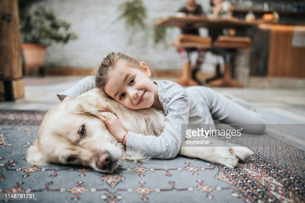 smiling girl and her golden retriever on carpet at home. - pets foto e immagini stock