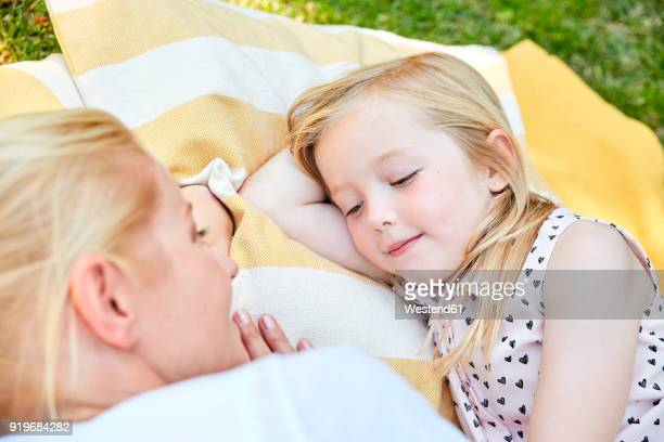 Smiling girl and mother lying on a blanket