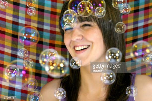 Souriant fille avec des bulles de savon arounded