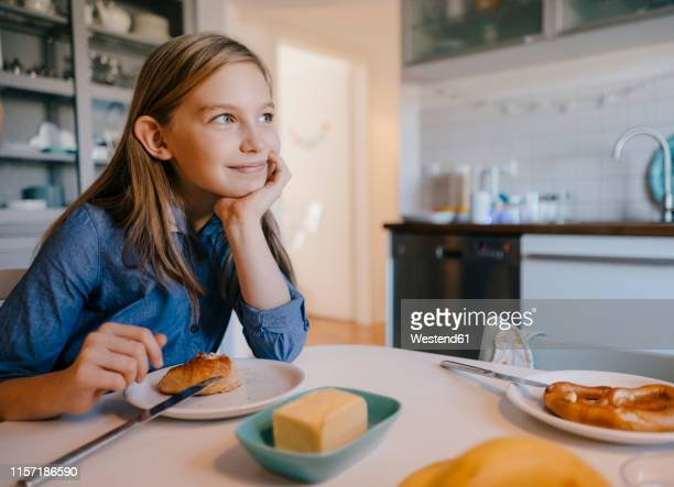 smiling girl at home sitting at breakfast table - nur kinder stock-fotos und bilder