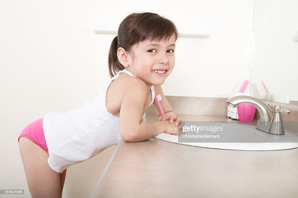 Smiling girl brushing teeth : Stock Photo