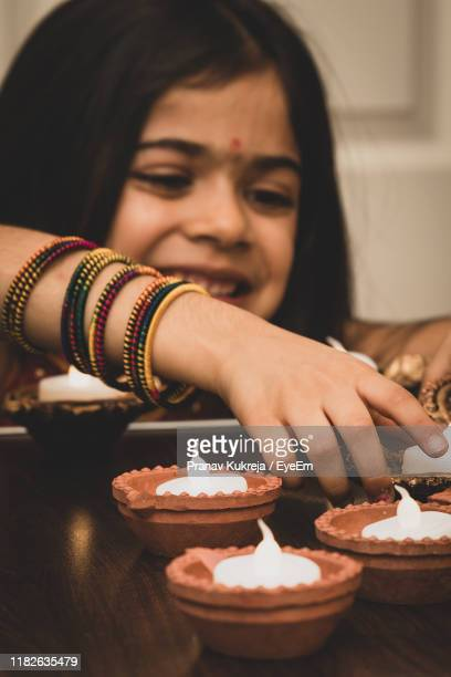 smiling girl burning diya at home - leicester stock pictures, royalty-free photos & images