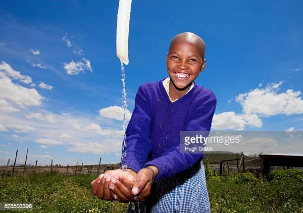 smiling girl (10-12) catching water from hose - hugh sitton 個照片及圖片檔