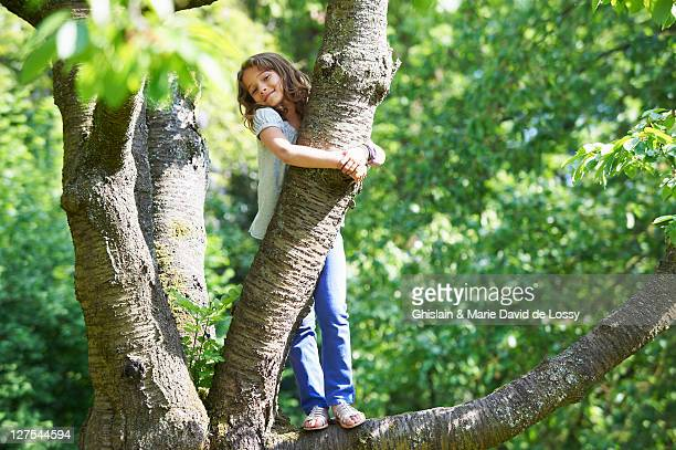 Smiling girl climbing tree outdoors