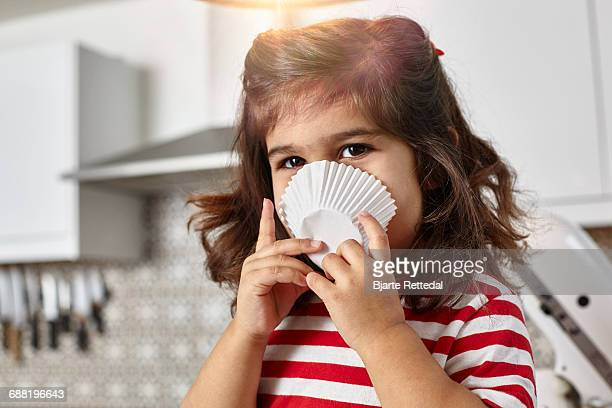 smiling girl covering face with cupcake liner - bjarte rettedal stock pictures, royalty-free photos & images