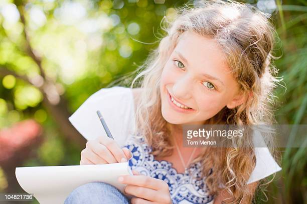 Smiling girl drawing on sketch pad