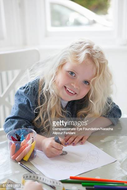 Smiling girl drawing with crayons