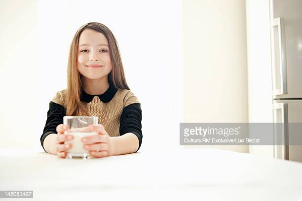 Smiling girl drinking milk in kitchen